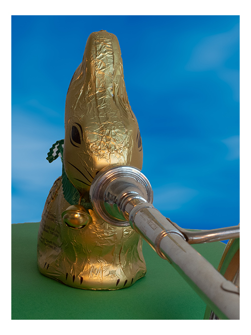gold wrapped chocolate rabbit playing a cornet, close up on face