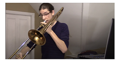 Photo of young man playing trombone, with a laptop nearby, in a small room