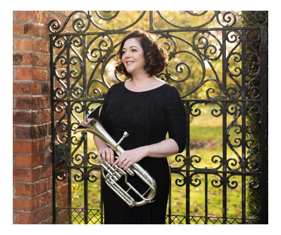 Photo of tenor horn player outside by formal garden gate